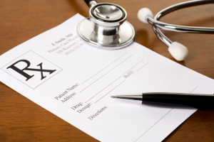 A prescription form, pen, and stethoscope on a doctor's desk. The form was created by the photographer and all personal information on the form is fictitious.